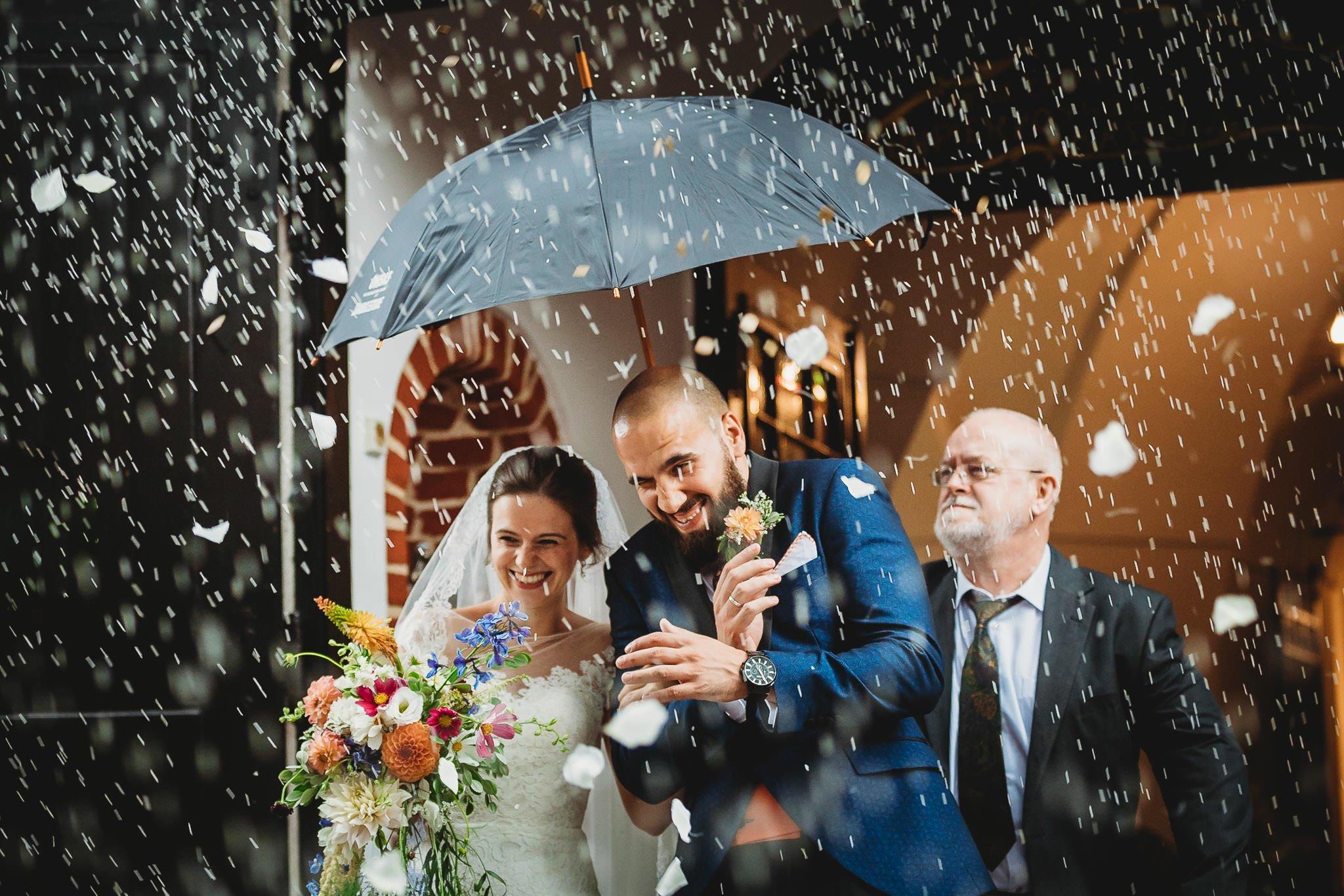 fotograf ślubny, Konin, para młoda obrzucona ryżem tuż po wyjściu z kościoła