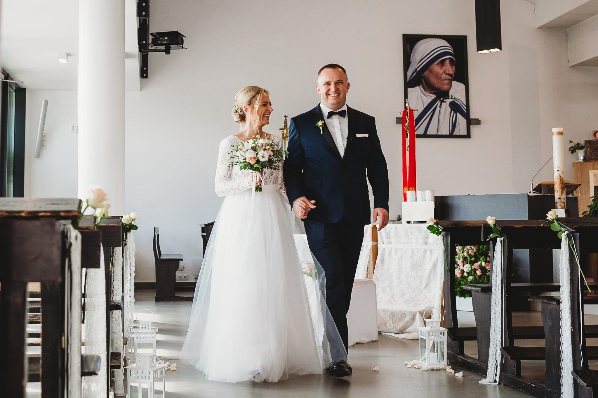 szczęśliwa para młoda z uśmiechem wychodzi z kościoła-fotograf ślubny poznań
